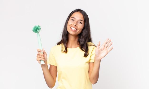 Jeune femme hispanique souriant joyeusement, agitant la main, vous accueillant et vous saluant et tenant une brosse à vaisselle