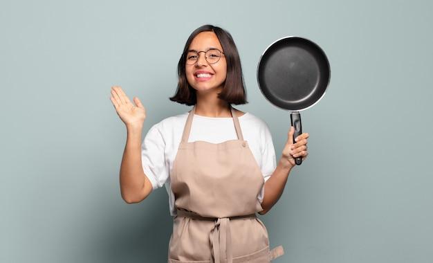 Jeune femme hispanique souriant joyeusement et gaiement, agitant la main, vous accueillant et vous saluant