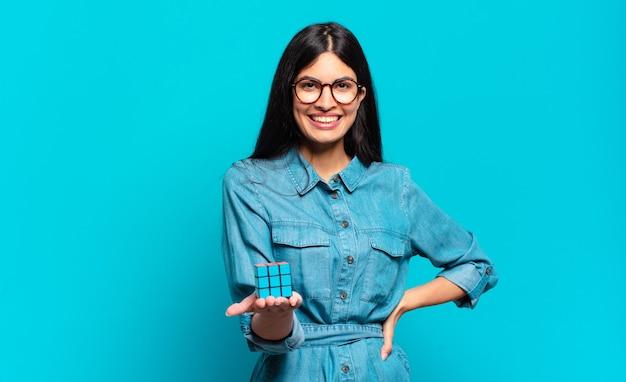 Jeune femme hispanique souriant joyeusement avec une main sur la hanche et une attitude confiante, positive, fière et amicale