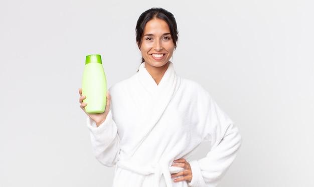 Jeune femme hispanique souriant joyeusement avec une main sur la hanche et confiante portant un peignoir et tenant un shampoing