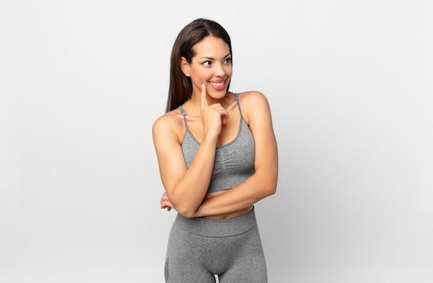Jeune femme hispanique souriant joyeusement et rêvant ou doutant. concept de remise en forme