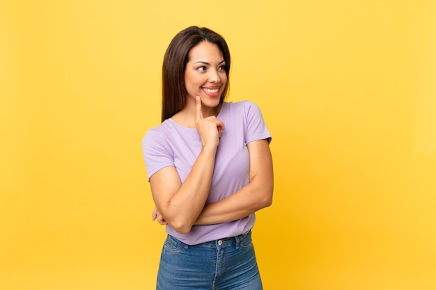 Jeune femme hispanique souriant joyeusement et rêvant ou doutant