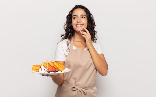Jeune femme hispanique souriant joyeusement et rêvassant ou doutant, regardant sur le côté