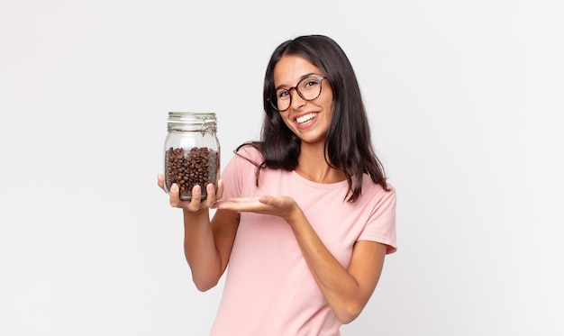 Jeune femme hispanique souriant joyeusement, se sentant heureuse et montrant un concept et tenant une bouteille de grains de café
