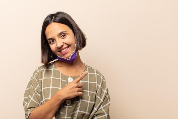 Jeune femme hispanique souriant joyeusement, se sentant heureuse et pointant vers le côté et vers le haut