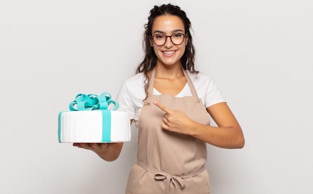 Jeune femme hispanique souriant joyeusement, se sentant heureux et pointant vers le côté et vers le haut, montrant l'objet dans l'espace de copie