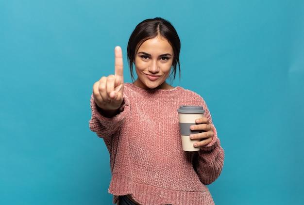 Jeune femme hispanique souriant et à la sympathique, montrant le numéro un ou d'abord avec la main en avant, compte à rebours