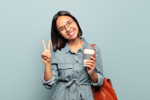 Jeune femme hispanique souriant et à la sympathique, montrant le numéro deux ou seconde avec la main en avant, compte à rebours