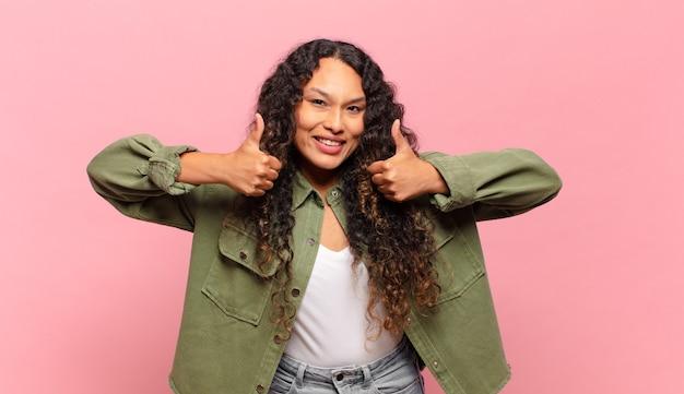Jeune femme hispanique souriante ayant l'air heureuse, positive, confiante et réussie, avec les deux pouces vers le haut