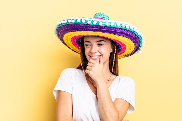 Jeune femme hispanique souriante avec une expression heureuse et confiante avec la main sur le menton. concept de chapeau mexicain
