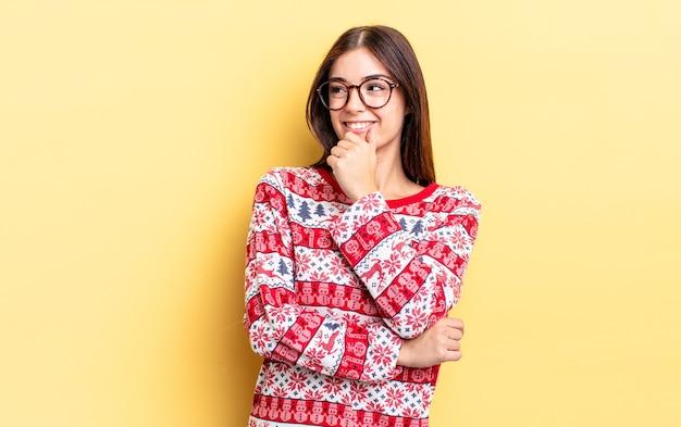 Jeune femme hispanique souriante avec une expression heureuse et confiante avec la main sur le menton. concept de noël et nouvel an