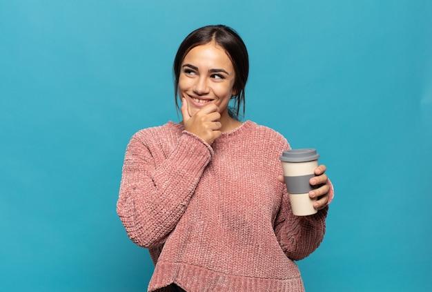 Jeune femme hispanique souriante avec une expression heureuse et confiante avec la main sur le menton, se demandant et regardant sur le côté