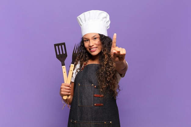 Jeune femme hispanique souriante fièrement et avec confiance faisant triomphalement la pose numéro un, se sentant comme un leader. concept de chef de barbecue