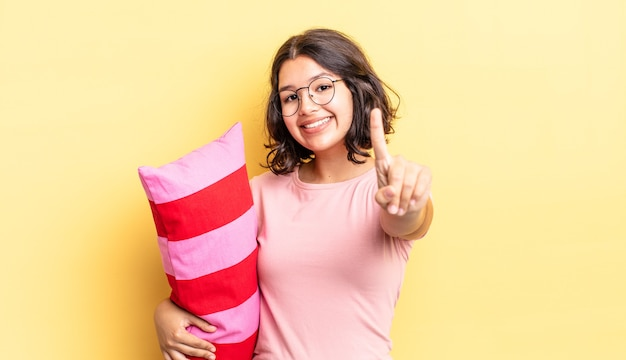 Jeune femme hispanique souriante fièrement et en toute confiance faisant numéro un. concept de réveil matinal