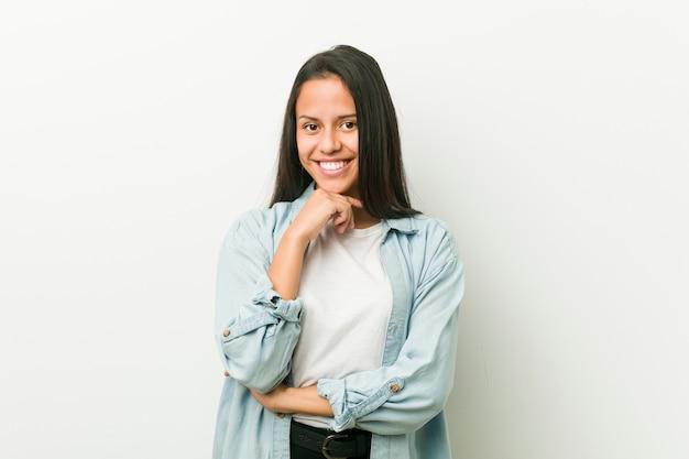 Jeune femme hispanique souriante heureuse et confiante, toucher le menton avec la main.