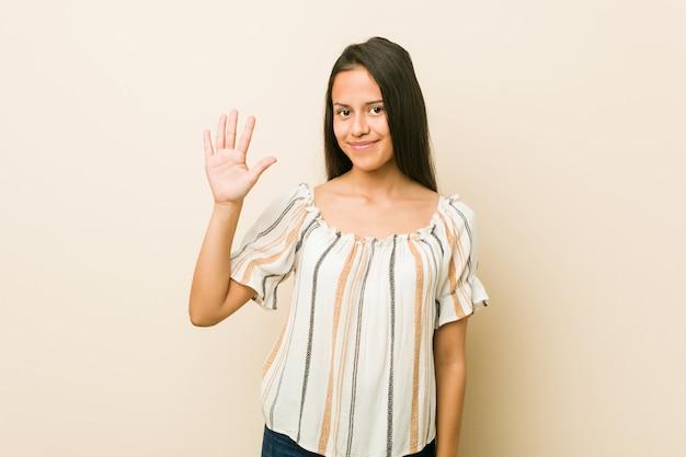 Jeune femme hispanique souriante joyeuse montrant le numéro cinq avec les doigts.