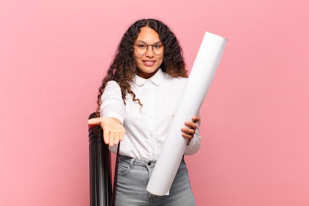 Jeune femme hispanique souriante joyeusement avec un regard amical, confiant et positif, offrant et montrant un objet ou un concept. concept d'architecte