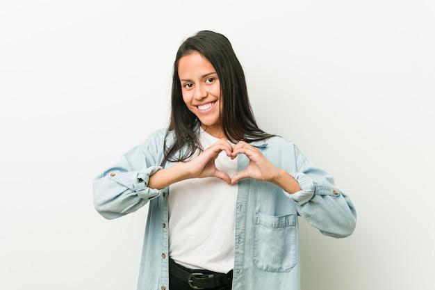 Jeune femme hispanique souriante et montrant une forme de coeur avec les mains.