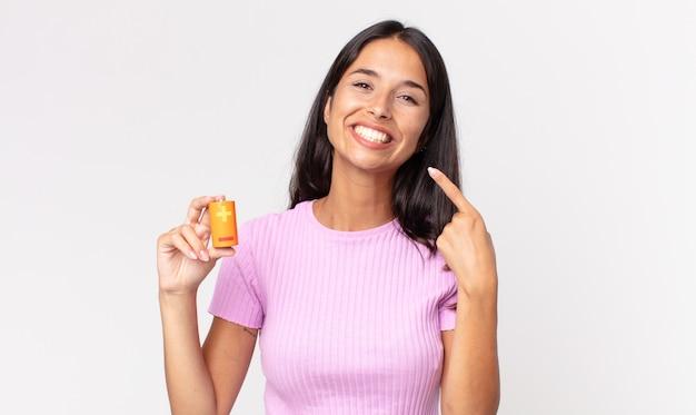Jeune femme hispanique souriante pointant avec confiance vers son large sourire et tenant des batteries