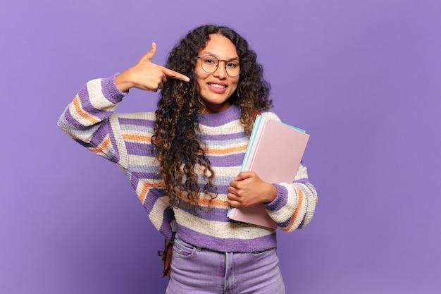 Jeune femme hispanique souriante pointant avec confiance vers son propre large sourire, attitude positive, détendue et satisfaite. concept d'étudiant