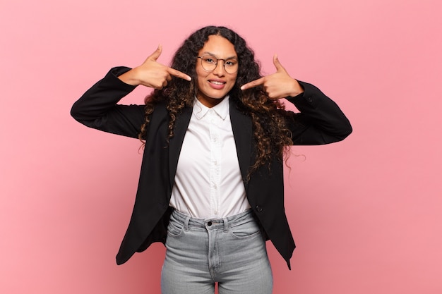 Jeune femme hispanique souriante pointant avec confiance vers son propre large sourire, attitude positive, détendue et satisfaite