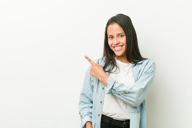 Jeune femme hispanique souriante et pointant à côté, montrant quelque chose dans un espace vide.