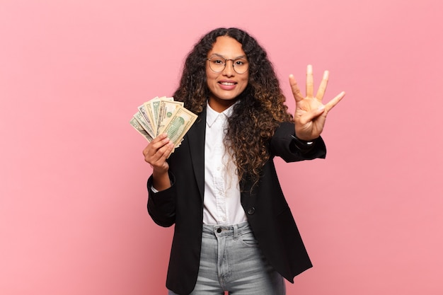 Jeune femme hispanique souriante et à la recherche amicale, montrant le numéro quatre ou quatrième avec la main en avant, compte à rebours. concept de billets en dollars