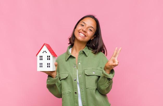 Jeune femme hispanique souriante et à la recherche heureuse, insouciante et positive, gesticulant la victoire ou la paix d'une main
