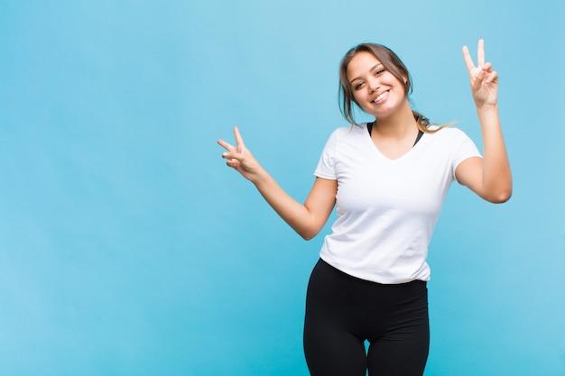 Jeune femme hispanique souriante et à la recherche heureuse, sympathique et satisfaite, faisant des gestes la victoire ou la paix à deux mains