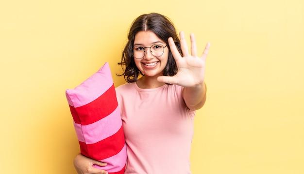 Jeune femme hispanique souriante et semblant amicale, montrant le numéro cinq. concept de réveil matinal