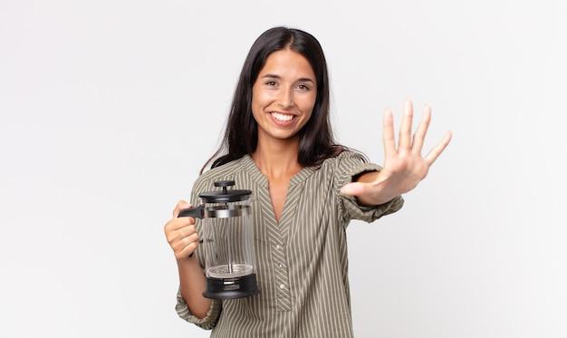 Jeune femme hispanique souriante et semblant amicale, montrant le numéro cinq et tenant une cafetière manuelle