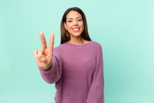 Jeune femme hispanique souriante et semblant amicale, montrant le numéro deux