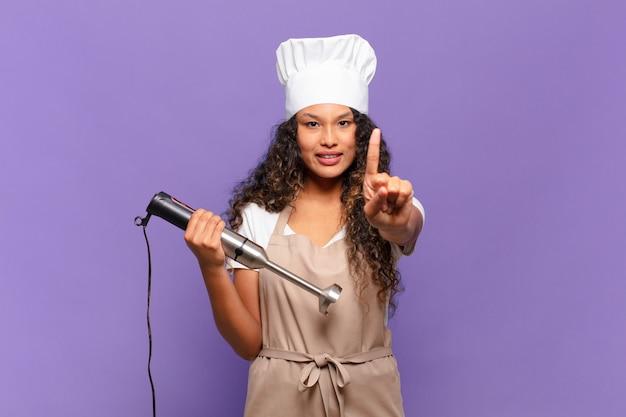 Jeune femme hispanique souriante et semblant amicale, montrant le numéro un ou le premier avec la main en avant, compte à rebours