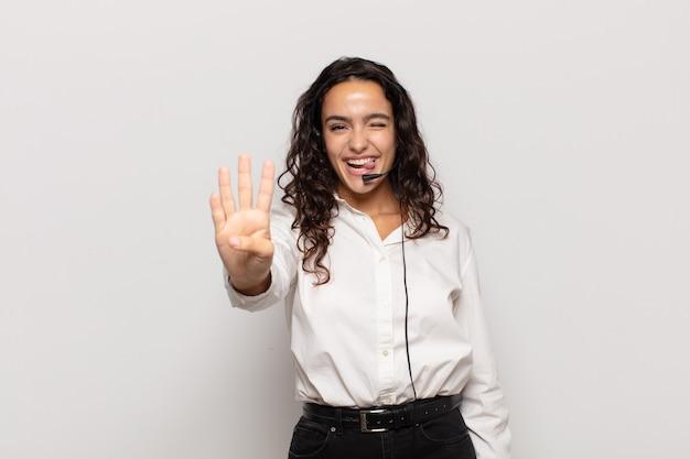 Jeune femme hispanique souriante et semblant amicale, montrant le numéro quatre ou quatrième avec la main vers l'avant, compte à rebours