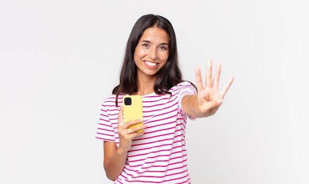 Jeune femme hispanique souriante et semblant amicale, montrant le numéro quatre et tenant un smartphone