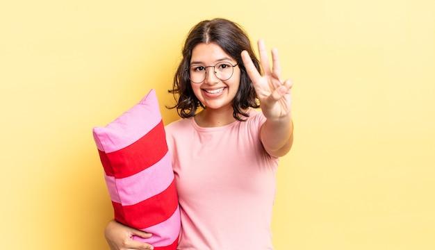 Jeune femme hispanique souriante et semblant amicale, montrant le numéro trois. concept de réveil matinal