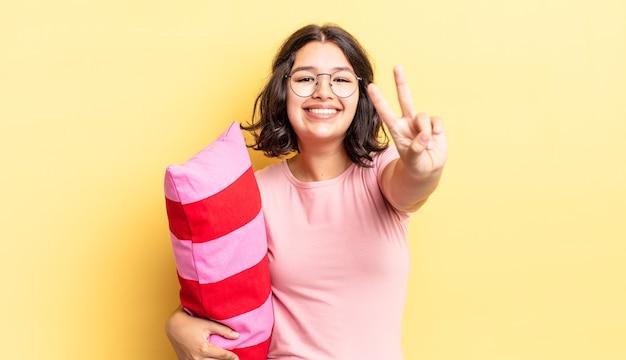 Jeune femme hispanique souriante et semblant heureuse, gesticulant la victoire ou la paix. concept de réveil matinal
