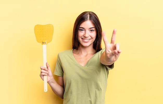 Jeune femme hispanique souriante et semblant heureuse, gesticulant la victoire ou la paix. tuer les mouches concept