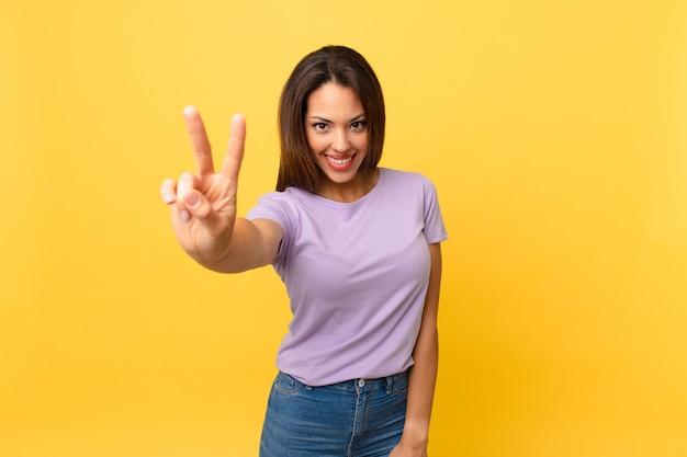 Jeune femme hispanique souriante et semblant heureuse, gesticulant la victoire ou la paix