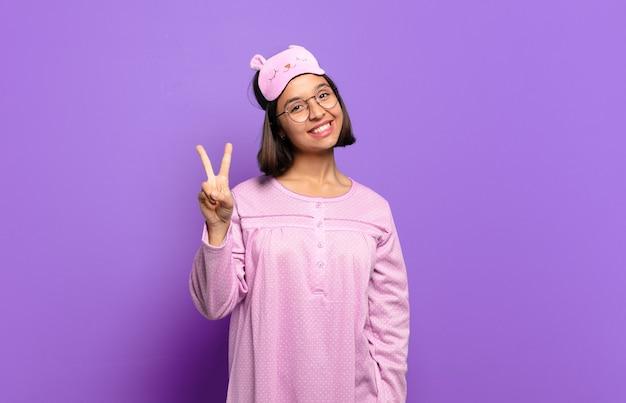 Jeune femme hispanique souriante et semblant heureuse, insouciante et positive, gesticulant la victoire ou la paix d'une main