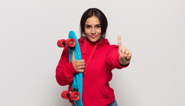 Jeune femme hispanique souriante et à la sympathique, montrant le numéro un ou d'abord avec la main en avant, compte à rebours