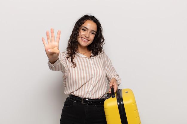 Jeune femme hispanique souriante et à la sympathique, montrant le numéro quatre ou quatrième avec la main en avant, compte à rebours