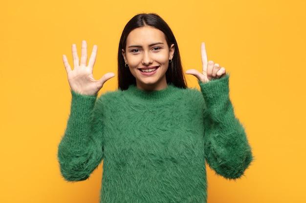Jeune femme hispanique souriante et à la sympathique, montrant le numéro sept ou septième avec la main en avant, compte à rebours