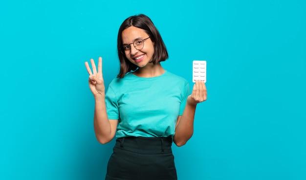 Jeune femme hispanique souriante et à la sympathique, montrant le numéro trois ou troisième avec la main en avant, compte à rebours