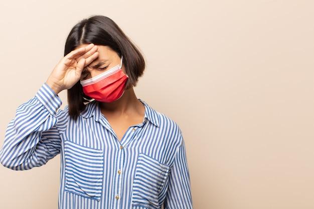 Jeune femme hispanique à stressé, fatigué et frustré, séchant la sueur du front, se sentant désespérée et épuisée