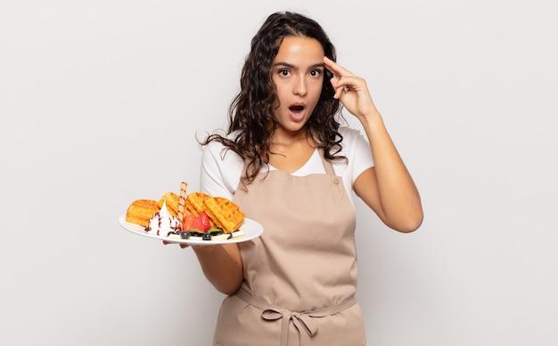 Jeune femme hispanique à la surprise, la bouche ouverte, choquée, réalisant une nouvelle pensée, idée ou concept
