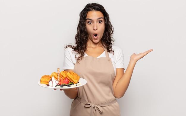 Jeune femme hispanique à la surprise et choqué, avec la mâchoire tombée tenant un objet avec une main ouverte sur le côté