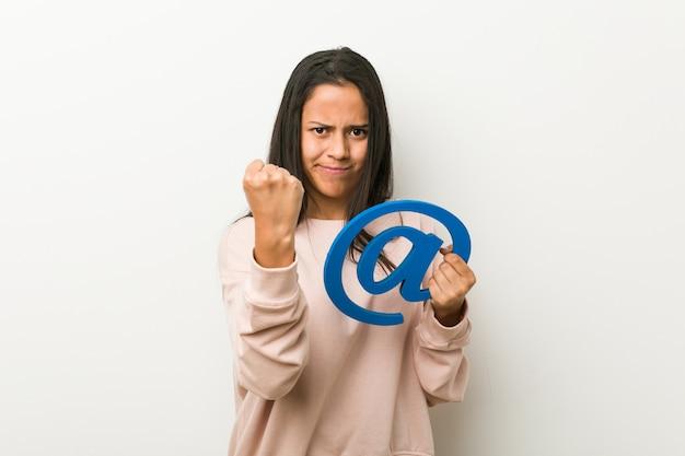 Jeune femme hispanique tenant un at icon montrant le poing à la caméra, expression faciale agressive