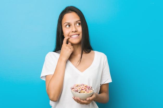 Jeune femme hispanique tenant un bol de céréales sucrées détendue pensant à quelque chose qui regarde une copie.