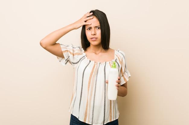 Jeune femme hispanique tenant une bouteille de crème choquée, elle se souvient d'une réunion importante.